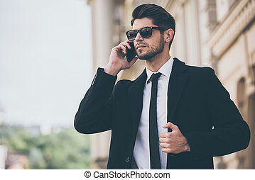 Important call. Handsome young well-dressed man in sunglasses talking on mobile phone and looking away while standing outdoors