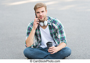 important call. phone call. listen music. ebook concept. man checkered shirt. student relax and recharge. coffee to go. guy drink coffee outdoor. man sit on ground. carefree student in headset