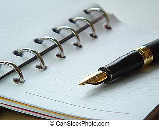 blank spiraled notebook with fountain pen on top of it