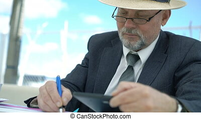Imposing old man writing down from tablet in cafe. 4K.