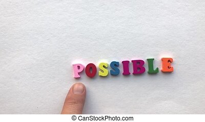 impossible. coloured wooden letters on a white sheet of...