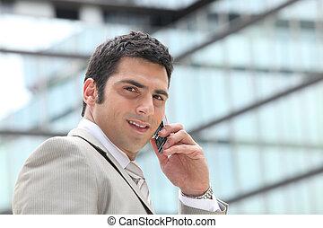 imprenditore, usando, uno, cellphone, esterno, uno, rispecchiato, costruzione