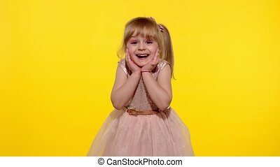 Impressed child. Perfect surprise. Exciting news. Wow reaction. Portrait of happy amazed astonished young kid girl in shiny dress isolated on yellow copy space background. Slow motion. 6k downscale