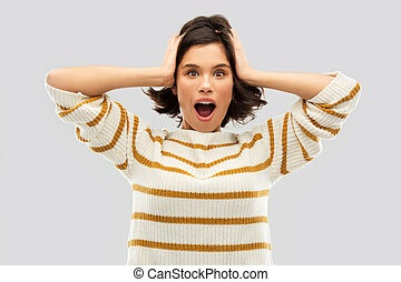 impressed woman in pullover holding to her head
