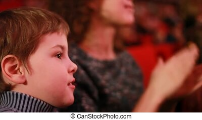 Impressionable little boy sits on a red chair in auditorium of circus and watches a show