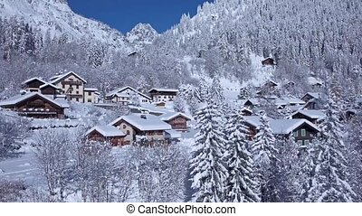 Impressive aerial drone view on snow covered roof of small cozy luxury villa in winter forest in Alps mountain landscape