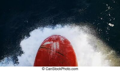 Impressive closeup of a large ship bow moving forward and cutting the foamy sea waves on a sunny day in autumn