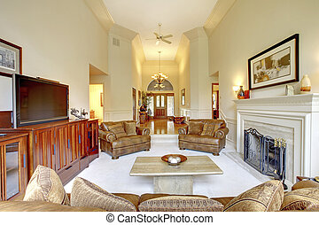 Impressive high ceiling living room in luxury house. View of hallway with entrance door.