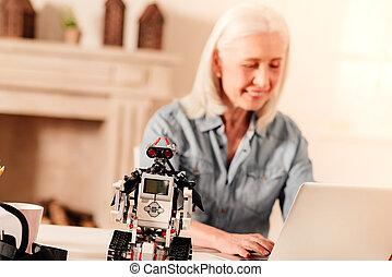 Impressive robot standing on table of elderly lady