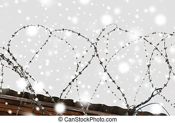 barb wire fence over gray sky and snow