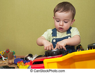 Improving the car wheel - A little boy is playing with the ...