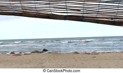 Improvised driftwood Beach shelter hut at sandy seaside