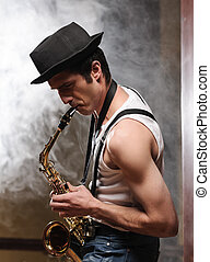 Improvising with his saxophone. Handsome young jazz man ...