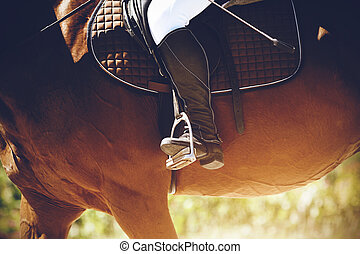 In a black boot, the foot of a rider bases on a stirrup, sitting astride a Bay horse in the bright light of the summer sun.