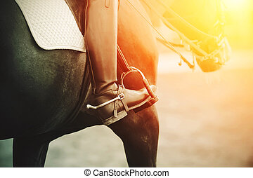 In a black boot with a spur, the foot of a rider sitting astride a Bay racehorse in the sunlight.