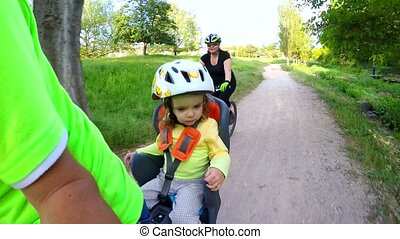In a children's armchair, a child is riding a bicycle. Slow motion.