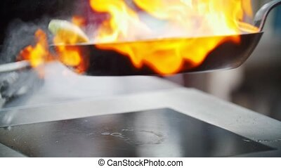 In a frying pan fry onions, burning fire, looks spectacular,...