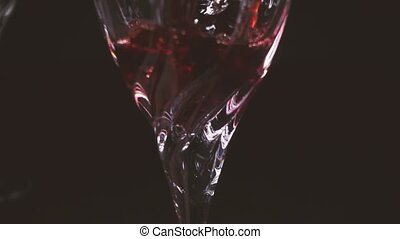 In a glass on a black background, wine is poured from the decanter slow mo