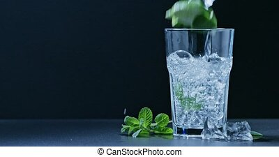 In a glass pour a cold drink with mint, lime and ice . Slow...