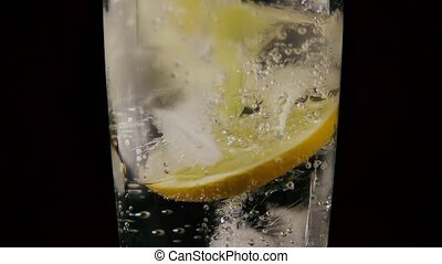 In a glass with soda ice and lemon drop the straw. Slow motion