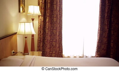 in a hotel room with a lamp and a double bed and lamps