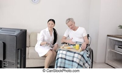 In a Local Hospital a Nurse Looks After a Gray Haired Man in...