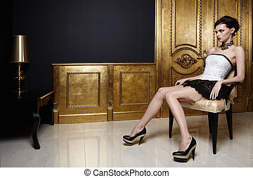 The beautiful girl sits in an armchair in a magnificent interior