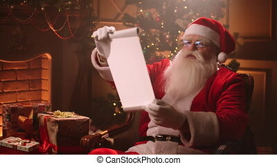 In a magical atmosphere Santa Claus reads a paper scroll with a list of children for gifts.