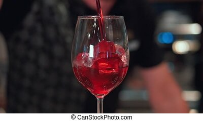 In a nightclub or pub a bartender preparing a cocktail with...