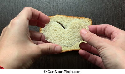 in a piece of bread carved heart on a dark background - in a...
