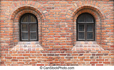 In a red brick wall of the medieval castle there are two narrow windows