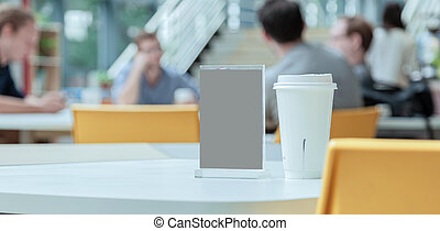 In a scene from a coffee shop. White table and orange seats. Table cards on the table, and white coffee paper cups. I made a mark on the coffee cup again.