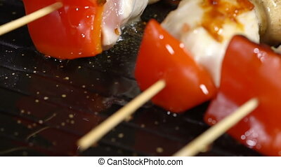 In a skillet with skewers pour oil. Slow motion - Olive oil...