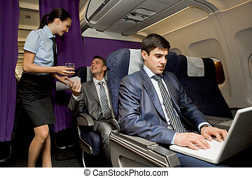 In airplane - Image of busy male typing on laptop with...