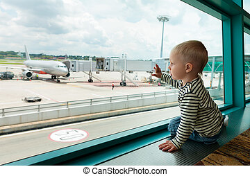 In airport hall child looks at the plane through window -...