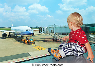 In airport hall child looks at the plane through window