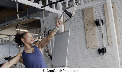 In an afro training woman does exercises on suspended TRX belts in gym.