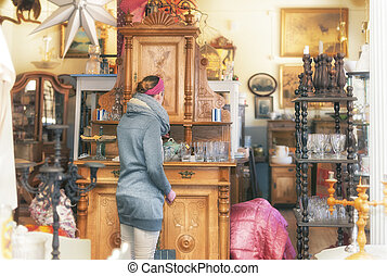 In an antique shop - Attractive woman visiting an antique...