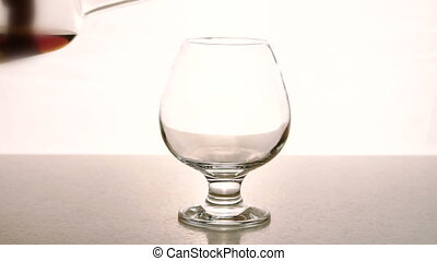 In an empty glass from bottle alcohol is poured on white background.