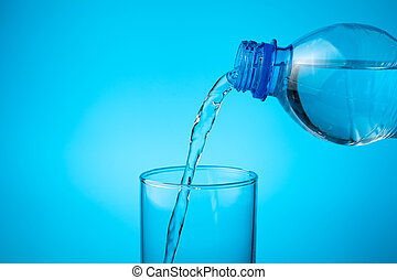 In an empty glass, pour fresh water on a blue background.