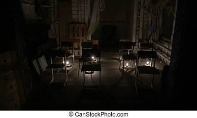 In an empty room lights are lit, chairs on the stage
