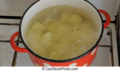 In an old red pot, potatoes are brewed, gas stove