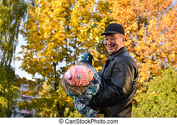 In autumn grandfather and granddaughter