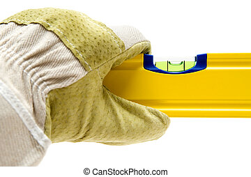 In Balance - Gloved hand holding a spirit level. Isolated on...