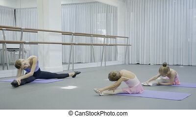 In ballet studio female coach shows young girls slopes of sitting.