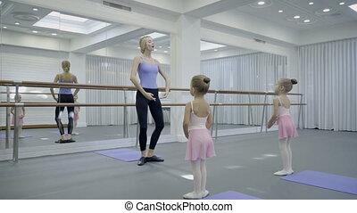 In ballet studio teacher shows children dancing movements near mirror.