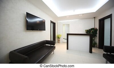 In beauty salon hall there are two black sofas and reception