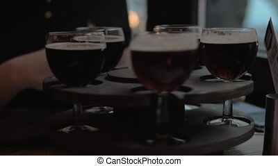 In cafe on table is a rotating tray of drinks, girl twists the tray and selects a glass