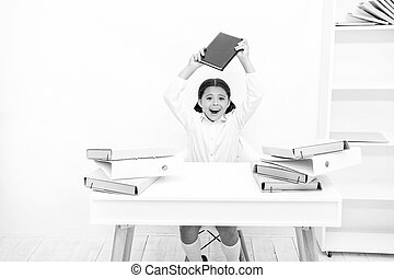 In capricious mood. Naughty child being noisy at school. Little child refusing to learn literacy. Small girl raising book over head. Angry girl hates reading book. Schoolgirl having literature lesson