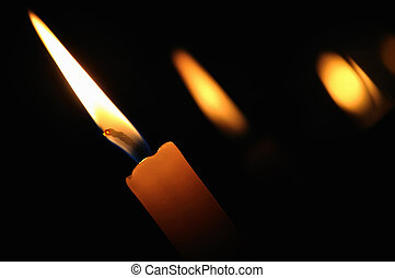 A burning candle in the church on a dark background